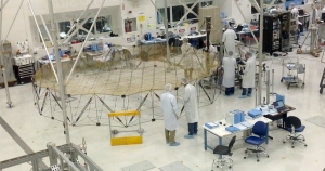 Technicians assemble and test the SMAP (Soil Moisture Active Passive) probe inside the large clean room at the Jet Propulsion Laboratory.