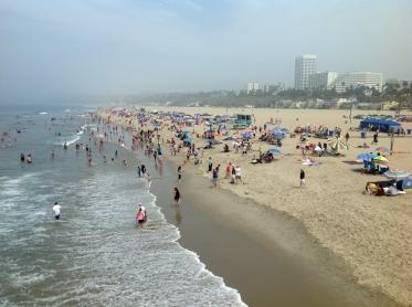 Santa Monica beach as seen from the pier. The usual summer haze fades away the Malibu Hills.